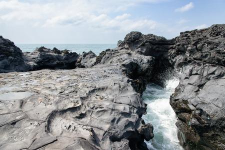 Landschaft mit Spray von Wasser durch Meerwasser schlug durch den Tunnel zwischen den Felsen an der Küste in der Nähe der Olle Trail Route 16 in Jeju Island, Korea. Standard-Bild - 39483228