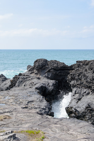 struck: landscape with Spray of water by struck Seawater through tunnel between rocks at the coast near the Olle trail route 16  in Jeju Island, Korea.
