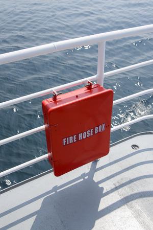 passenger ship: red fire hos box on the banister of a passenger ship