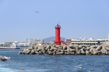 seawall: red Lighthouse on a seawall in the Moseulpo in Jeju Island, Korea. Editorial