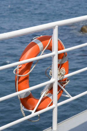 banister: Orange colored lifebelt and rope hang on a white banister a passenger ship