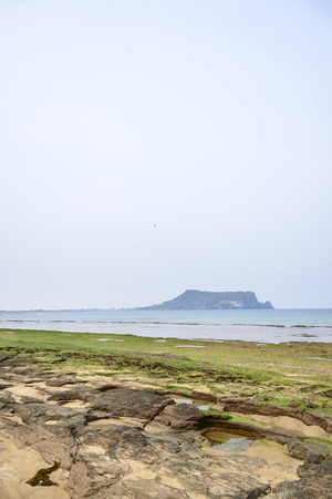 Landscape of Gwangchigi beach with Seongsan Ilchulbong, view from Olle trail No. 1. Gwangchigi is a unusual rocks beach and Ilchulbong is a volcanic cone located on the eastern end of Jeju Island. photo