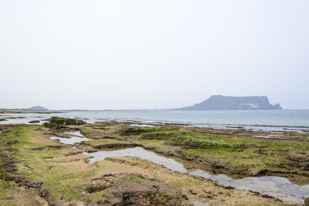 end of the trail: Landscape of Gwangchigi beach with Seongsan Ilchulbong, view from Olle trail No. 1. Gwangchigi is a unusual rocks beach and Ilchulbong is a volcanic cone located on the eastern end of Jeju Island.