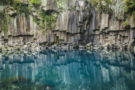 Cheonjeyeon No. 1 cascade. Cheonjeyoen falls (means the pond of God) consists of 3 falls. A variety of plant life, inclued Psilotum nudun, thrives around the falls. It is one of the most famous cascade in Jeju Island, in Korea. in first cascade, cliff is