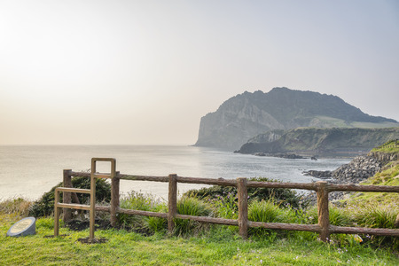 Landscape of Seongsan Ilchulbong with olle trail symbol in a morning. Ilchulbong is a volcanic cone located on the eastern end of Jeju Island and it means the Sunrize peak.