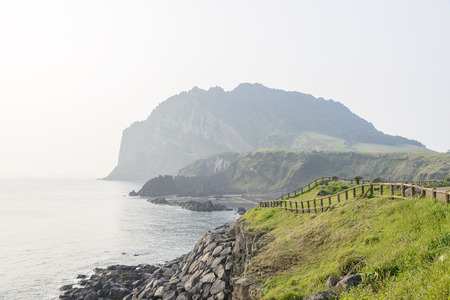 Landscape of Seongsan Ilchulbong, view from Olle trail No. 1 in a morning. Ilchulbong is a volcanic cone located on the eastern end of Jeju Island and it means the Sunrize peak. Imagens - 41491577