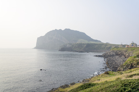 means to an end: Landscape of Seongsan Ilchulbong, view from Olle trail No. 1 in a morning. Ilchulbong is a volcanic cone located on the eastern end of Jeju Island and it means the Sunrize peak.