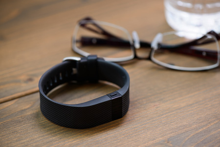 hrs: wearable device, wirst watch type Sports tracker and other objects on a wooden board
