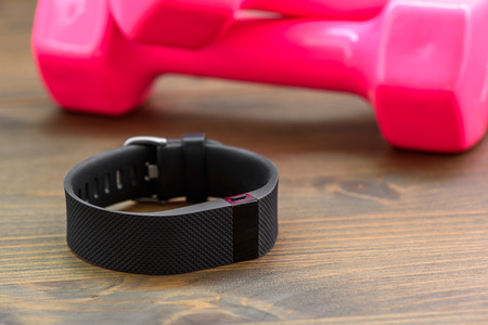 hrs: wearable device, wirst watch type Sports tracker and pink colored dumb-bell on a wooden board
