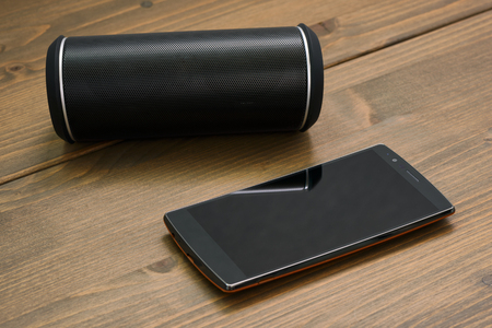 wireless: Curved touchscreen smartphone and Wireless portable bluetooth speaker on a wooden board