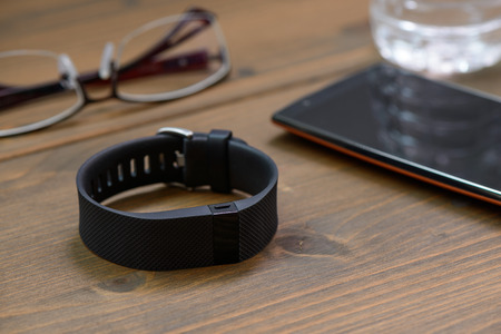 hrs: wearable device, wirst watch type Sports tracker and smart phone on a wooden board