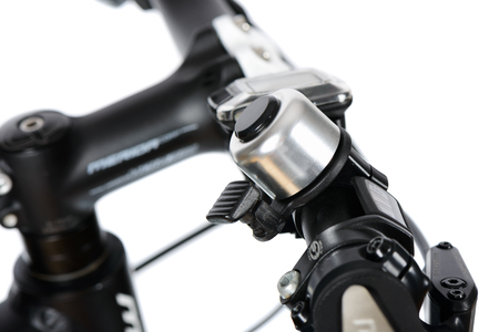handle bars: closeup of metal bike bell installed on a handle bar, isolated on white