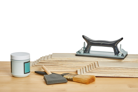 sandpaper: carpentry and painting tools, such as sandpaper holder, stack of veneers and paint brushes,  on a worktable