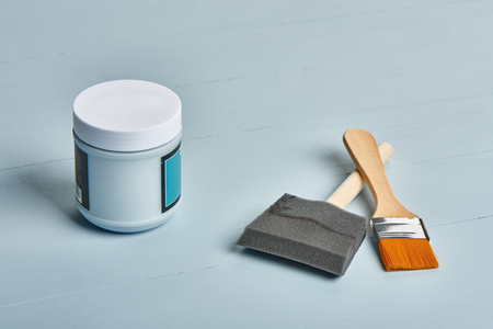 worktable: paintpot and two different type paint brushes on a worktable
