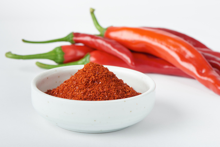 chili powder: closeup of Korean chili pepper powder with chili peppers, on a white background