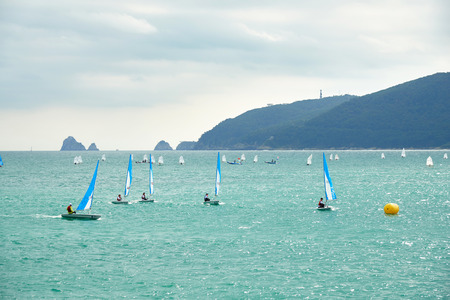consistently: Busan, Korea - September 19, 2015: Dinghy yachts on a Suyeong bay. The Busan Yachting Center is located at the seaside of Suyeong bay and sailing competitions are held at the bay consistently.