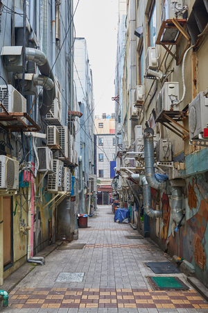 squalid: dirty alleyway with lots of aircon outdoor units on building wall. Stock Photo