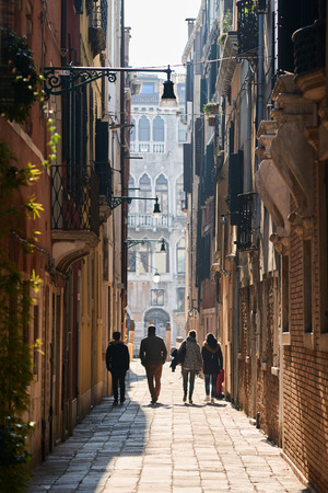 archtecture: Venice, Italy - Febuary 19, 2016: Walking people in Venice. Venice is a city famous for its settings, archtecture and artwork. A part of Venice is resignated as a World Heritage site.