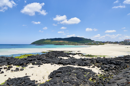 Hamdeok beach and Seoubong peak in Jeju, Korea. Hamdeok Beach is famous for its clean and blue water and white sand. And Seoubong is a peak near the Hamdeok beach and part of Olle trail course No.19. Фото со стока