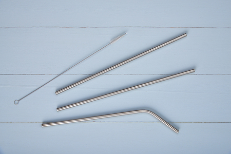 reusable straight and bent stainless steel straws o n a table