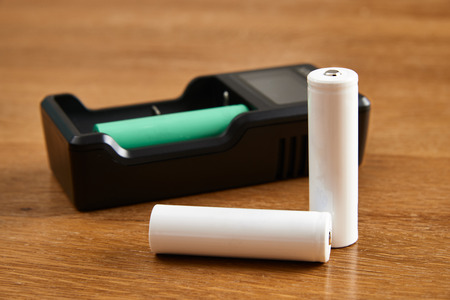 18650 Li-ion battery and charger on a wooden table