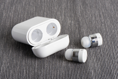 wireless cordless earbuds with chargeable case on a fabric background