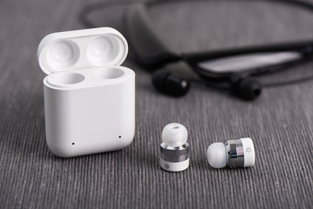 wireless cordless earbuds with chargeable case on a background of neck band type earphone Imagens
