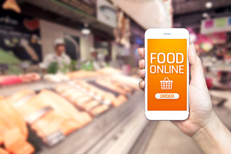 Mano che tiene mobile con generi alimentari in linea sullo schermo con sfondo sfocato supermercato, cibo concetto di consegna on-line. Archivio Fotografico
