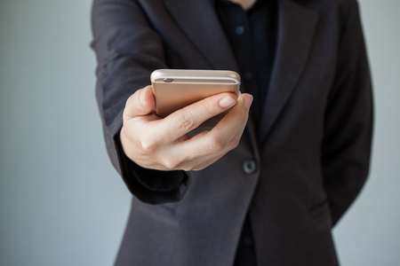 mobile telephone: Business woman hand holding mobile phone. Business woman working on a digital tablet. Business woman show cell telephone in black dressed suit on white background, Close up hand man use mobile phone