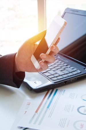 Gente de negocios con tecnología de telefonía móvil. Escribir la pantalla del teléfono inteligente. Hombre de negocios manos ocupadas utilizando teléfono celular en el escritorio de la Oficina, joven estudiante escribiendo en el teléfono sentado en la mesa de madera,