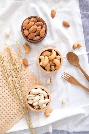 Mix of nuts in wooden bowl. Varieties of nuts with fork and spoon wood and Ears of rice on fabric.
