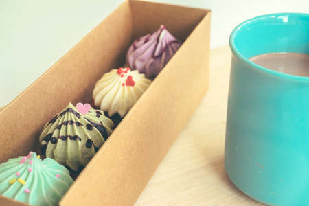 Sweet colorful pastel cupcakes in the box with a cup of chocolate drink ( vintage filter applied) photo