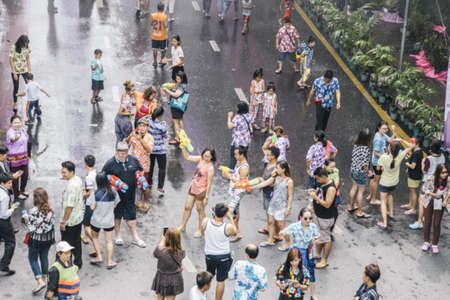enjoyed: BANGKOK,THAILAND-APRIL 12,2015: People enjoyed shooting water to each other on Songkran Festival or Thai New Year on Silom Road. (Blured and film filter applied ) Editorial