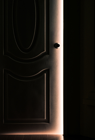 come back: White Door opening in the Dark Room with shining of sunlight - Concept image Stock Photo