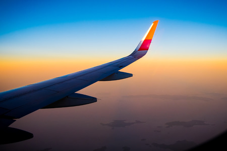 trip over: Aerial view of airplane fly during the sunset from windows plane - Flying over thailand - Colorful sunshine - Awesome lighting,silhouette Stock Photo