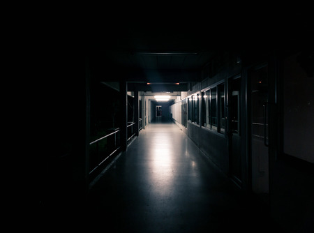 Dark corridor of the building with many door - Light shining from the end of corridor