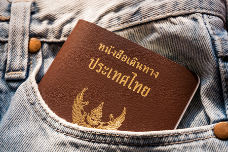 pickpocket: thailand passport in light denim jeans pocket - travel conept