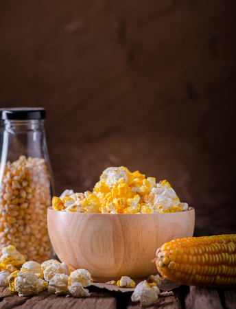 snacking: Pop corn and sweet corn on wooden background. Stock Photo