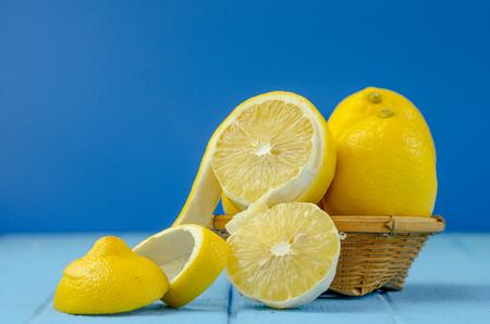 fresh lemons with Cut half on bule wooden background. Banco de Imagens