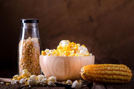 duo: Pop corn and sweet corn on wooden background. Stock Photo