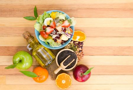 新鮮な野菜のサラダと木製のテーブルにフルーツ。