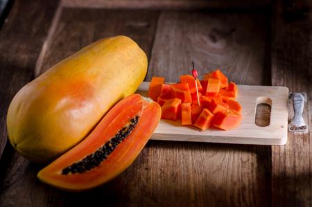 Half cut and whole papaya fruits on wooden table.