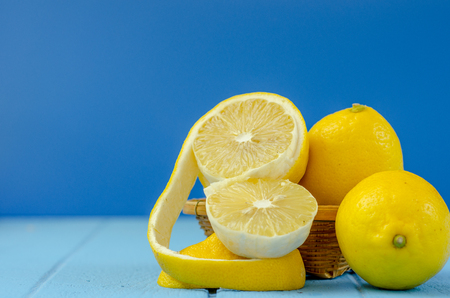 fresh lemons with Cut half on bule wooden background. Stock Photo