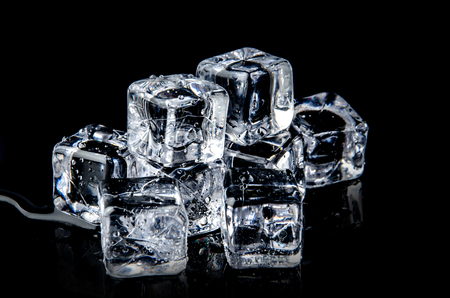 ice cube on the black background with reflection.