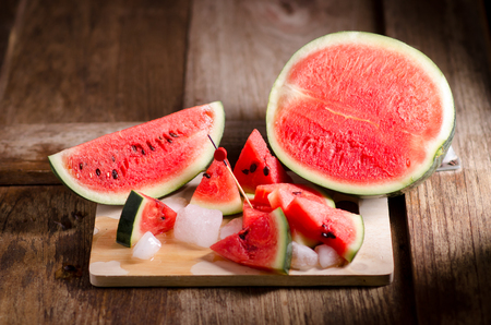 sliced watermelon: slice of watermelon on wooden table.