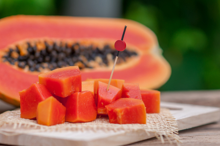 Sliced fresh Papaya fruit on wooden table with nature background.