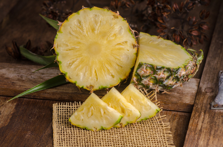 Sliced pineapple on wooden table.
