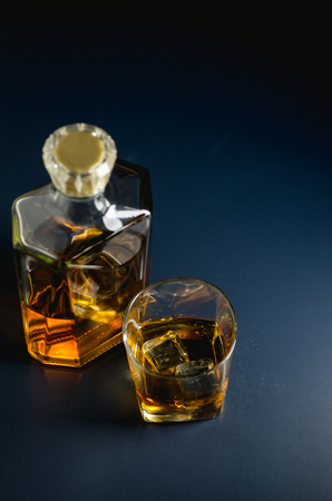 Whiskey glass and bottle on black and blue surface.