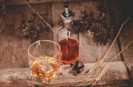 Glass of whiskey with ice decanter on wooden table. Stock fotó