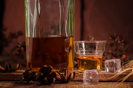 Glass of whiskey with ice decanter on wooden table. Stock Photo